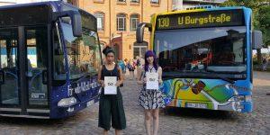 Cécile Debuc und Anna-Lena Kudritzki vor den Bussen, die nach ihren Entwürfen bemalt wurden.
