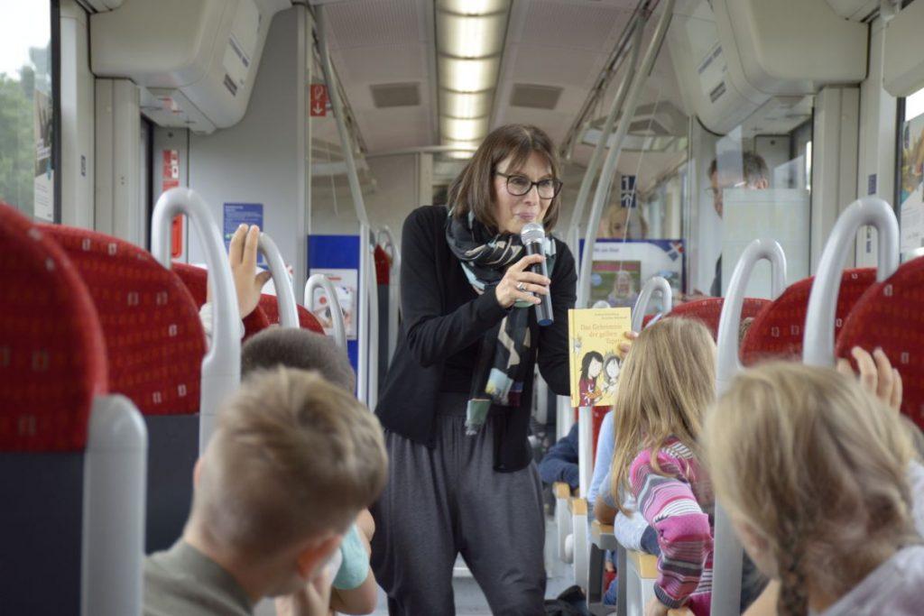 Die Autorin Andrea Schomburg las am 26. Juni 2018 im Rahmen des Hamburger Vorlesevergnügens in einer nordbahn zwischen Neumünster und Bad Oldesloe. Rund 40 Zweitklässler der Bad Oldesloer Klaus-Groth-Schule lauschten gebannt