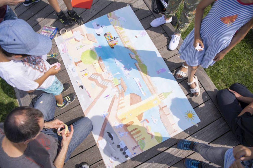 Wolfgang Slawski mit Schülerinnen und Schülern beim Vollenden des Wimmelbilds (Quelle: Hamburger VorleseVergnügen, Foto: Frank Siemers)